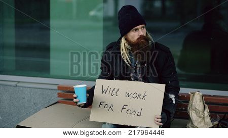 Homeless young man beg for money shaking cup to pay attention people walking near beggar at city street