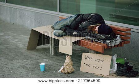 Young homeless drunk man preparing to sleep on cardboard on bench at sidewalk