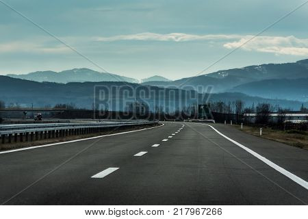 Two line wide highway on a cloudy winter day leading to the mountains through rural landscape