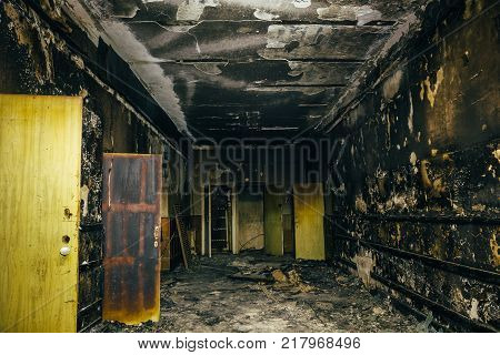Burned by fire interior of old building. Charred ash walls, doors and damaged furniture, dark toned