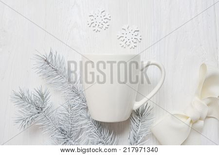 Mockup white cup on a wooden background, in Christmas decorations. The top view is photographed.