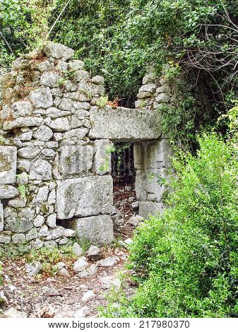 Ruins of the entrance of the ancient city of Olympos among the trees. Turkey