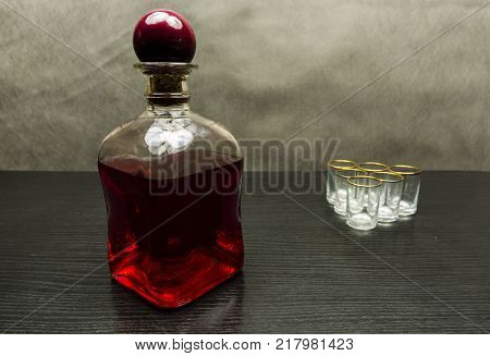 Bottle with cherry liqueur and empty glasses in the background.