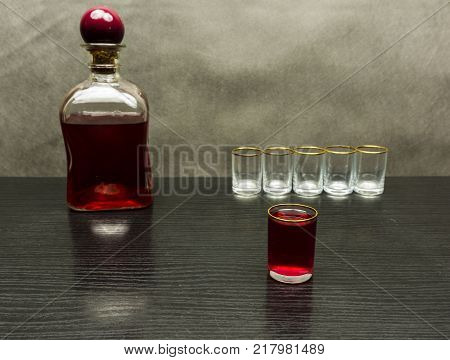 Glass of sweet cherry liqueur on a wooden table and a bottle in the background.