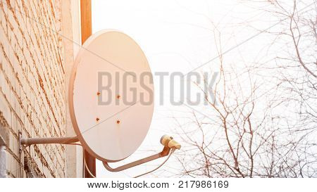 Satellite antenna dish on the brick wall of the house