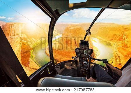 Helicopter cockpit scenic flight over Horseshoe Bend of Colorado River in Arizona, United States. Downstream from the Glen Canyon Dam and Lake Powell at sunset.