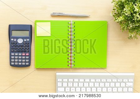 Top view office workplace with open green blank book sticky paper note calculator modern keyboard plants and premium pen on table background. To do list and planning projects ideas minimal style.