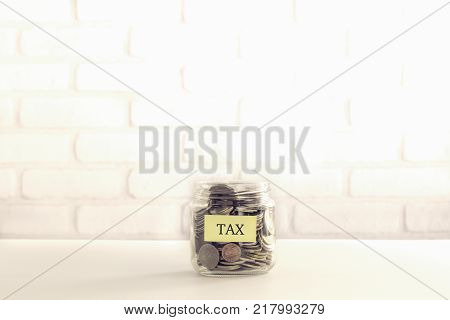 Yellow TAX label on saving money jar with world coins bricks background vintage retro style. Taxation of social welfare payments donation and economic crisis.