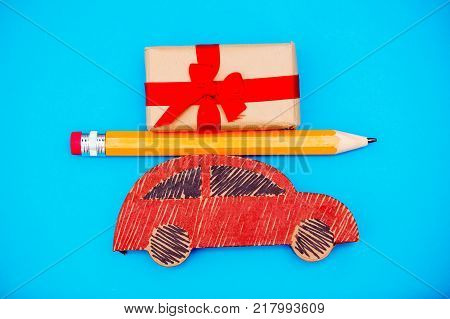 Red handmade car delivery with Christmas gift box and big pencil on blue background