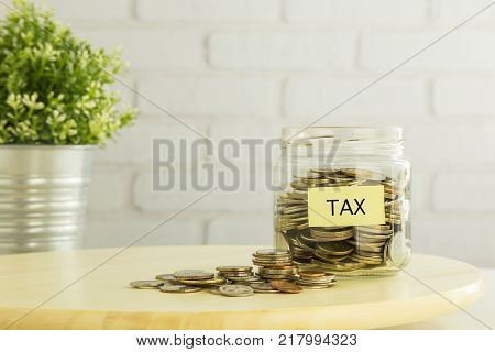 Coins in saving money jar and on wooden table with yellow TAX label plant pot and white bricks background. Tax planning strategies for individuals financial and accounting management.