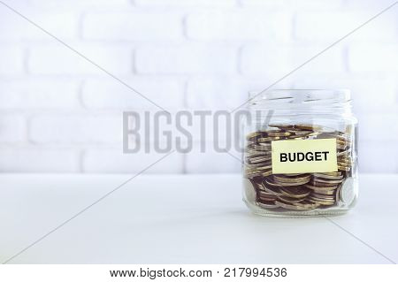 Coins In Money Glass Jar With Yellow Budget Tag Put On Table Bricks Background Vintage Retro Style.