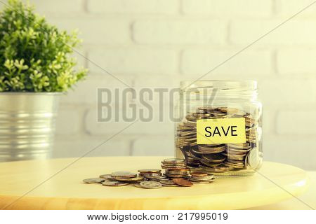 Coins In Saving Glass Jar And On Wooden Table With Yellow Save Tag Bricks And Plant Pot On Backgroun