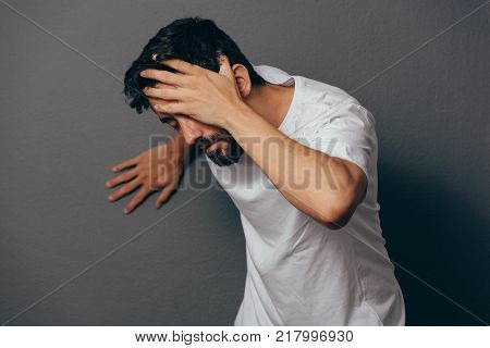 Man Suffering From Dizziness With Difficulty Standing Up While Leaning On Wall
