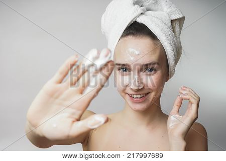 funny woman in a towel on the head happy cleanses the skin with foam on a white background isolated. Skincare cleansing concept poster