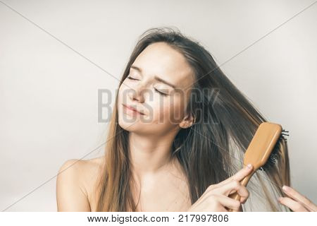smiling young girl combing her long hair with a wooden comb