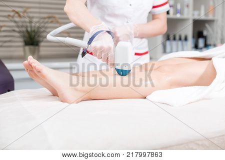 Doctor cosmetologist makes the procedure a young girl blonde. Laser epilation and cosmetology. Hair removal on ladies legs. at cosmetic beauty spa clinic. Cosmetology procedure from a therapist