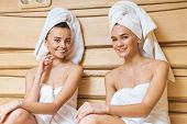 beautiful young women relaxing in sauna and looking at camera poster