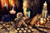 Voodoo doll, black candles, pentagram and old book on witch table. Occult, esoteric, divination and wicca concept. Mystic, voodoo and vintage background poster