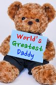 Cute teddy bear holding a blue sign that reads World's Greatest Daddy isolated on a white background poster