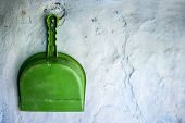 Green colored Dustpan hanging on the wall.Concept of cleanliness and neatness. poster