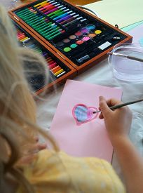 Child making Mother's Day card. Traditional play concept. A little girl paints a heart on a homemade greeting card as a gift for Mother's Day.