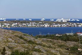 Newfoundland coastal town with modern hotel and icebergs; Fogo Island