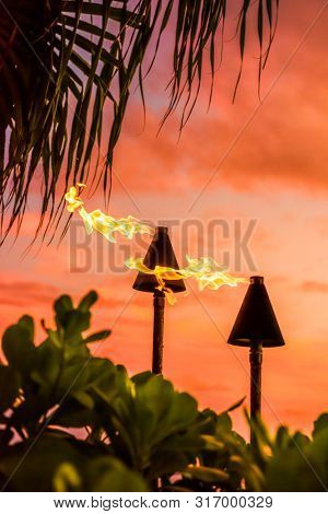 Hawaii luau party Maui fire tiki torches with flames burning against sunset sky clouds at night. Hawaiian culture travel background.