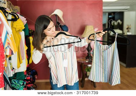 Female Customer Comparing Striped Tops Hanging From Coathangers In Shopping Mall