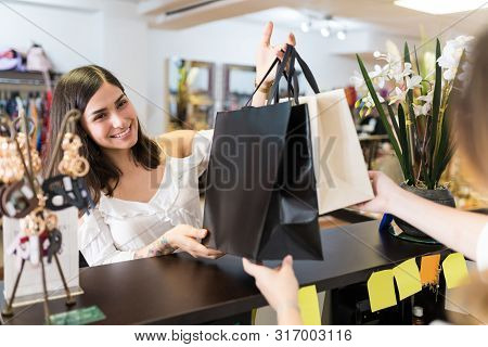 Smiling Beautiful Young Woman Receiving Shopping Bags From Shop Owner At Checkout