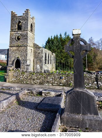 Gravestone in the shape of a Celtic cross with Saint Mary of the Rosary Catholic church in the background near Cong, County Mayo, Ireland poster