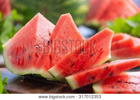 Summer ripe sliced watermelon. Juicy slice of ripe watermelon, close-up. Concept summer ripe berry on a wooden board. Watermelon and mint