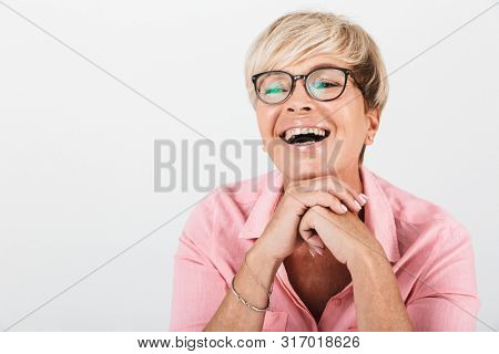 Portrait closeup of joyful middle-aged woman with short blond hair wearing eyeglasses smiling at camera isolated over white background