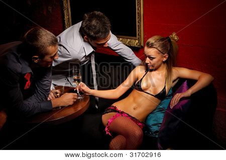 Drunk guys  flirting with stripteaser girl in night club