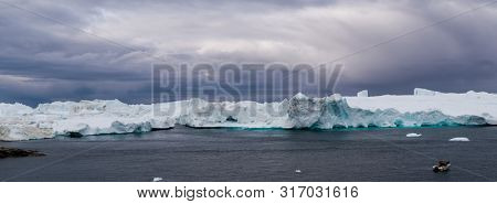 Global warming -Greenland Iceberg landscape of Ilulissat icefjord with giant icebergs. Icebergs from melting glacier. Arctic nature heavily affected by climate change