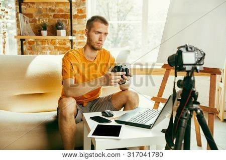 Young Caucasian Male Blogger With Professional Equipment Recording Video Review Of Camera At Home. B