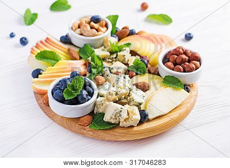 Cheese Platter With Assorted Cheeses, Blueberry, Apples, Nuts On White Table. Italian Cheese  Platte