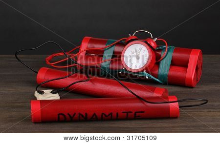 Timebomb made of dynamite on wooden table on grey background