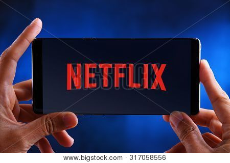 Poznan, Pol - Jul 10, 2019: Hands Holding Smartphone Displaying Logo Of Netflix, An American Media-s