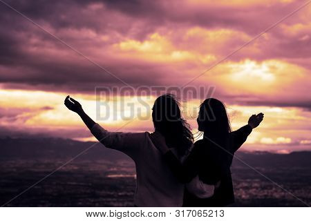 Christian Worship And Praise. Two Young Woman Are Praying And Worshiping In The Evening.