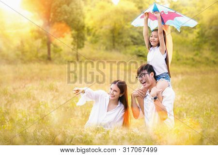 Asian Family Father, Mother And Daughter Play Ta Kite In The Outdoor Park With Sunrise And Goldent C