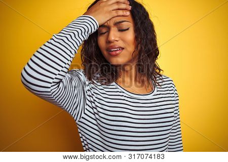 Transsexual transgender woman wearing striped t-shirt over isolated yellow background stressed with hand on head, shocked with shame and surprise face, angry and frustrated. Fear and upset