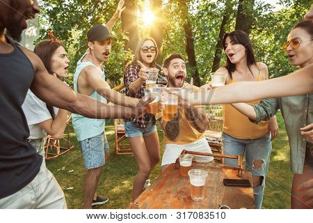 Group Of Happy Friends Having Beer And Barbecue Party At Sunny Day. Resting Together Outdoor In A Fo