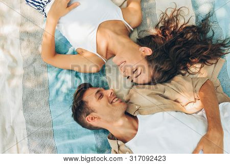 Above View Image Of Beautiful Couple In Love Dating Outdoors At The Park On A Sunny Day. Couple Lyin