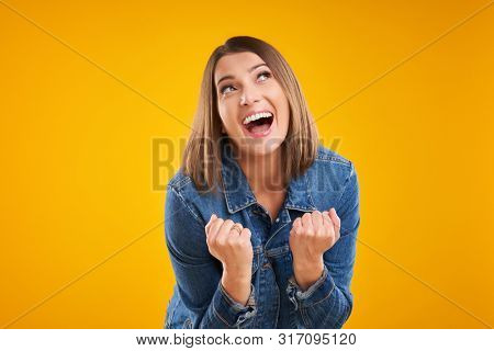 Close up of successfull woman in denim jacket over yellow background