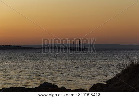 Ship At Sea On The Horizon At Sunset.a Beautiful Sea Sunset Or Sunrise And Sailing Ship On The Horiz