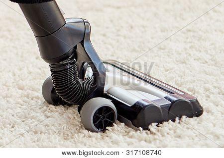Close Up Of Modern Vacuum Cleaner On Beige Carpet On Floor In Living Room, Copy Space. Housework, Ho