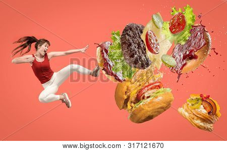 Fast Food. Young Caucasian Woman Fights With Unhealthy Nutrition. Kicks Burger Or Sandwich In Jump O