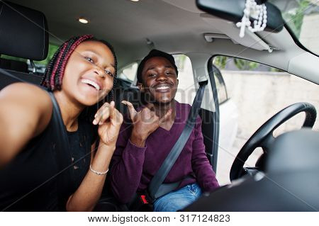 Beautiful Young African American Couple Sitting On The Front Passenger Seats While Handsome Man Driv