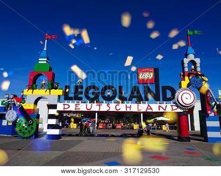 Entrance Gate To The Legoland Amusement Park In Günzburg, Germany.fireworks At Daytime Above The En
