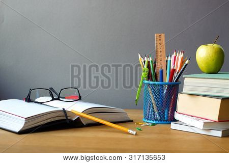 Back To School Concept, School Supplies, Stack Of Books, Green Apple And Open Book With Glasses On A